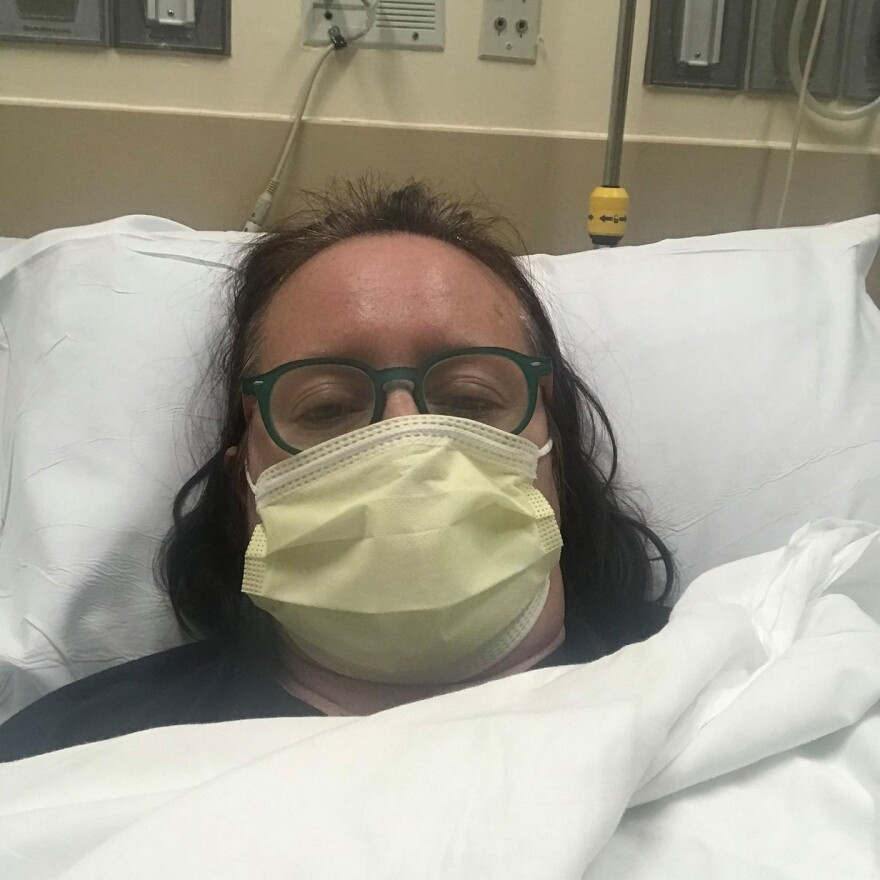 Close up of Christina Ray Stanton in a hospital bed wearing a face mask.