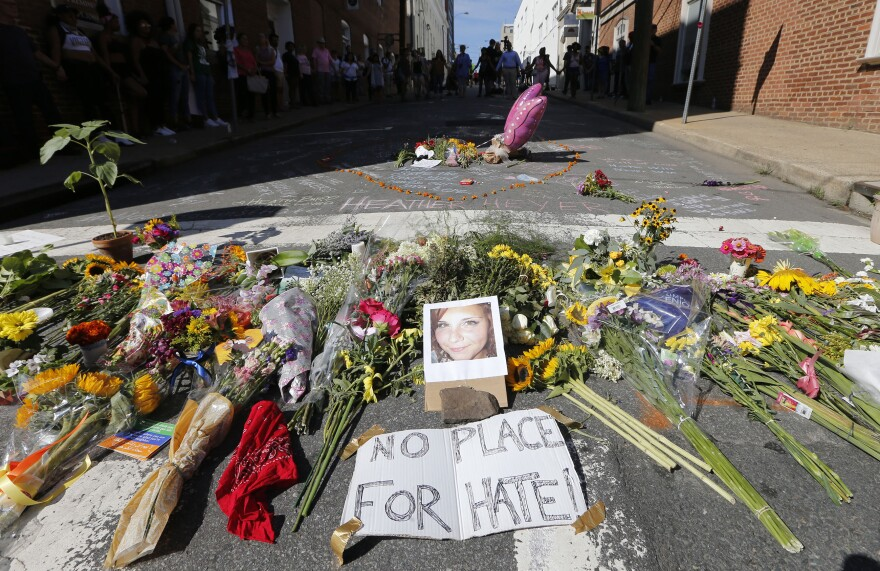 A makeshift memorial of flowers and a photo of victim, Heather Heyer, sits in Charlottesville, Va., Sunday, Aug. 13, 2017.