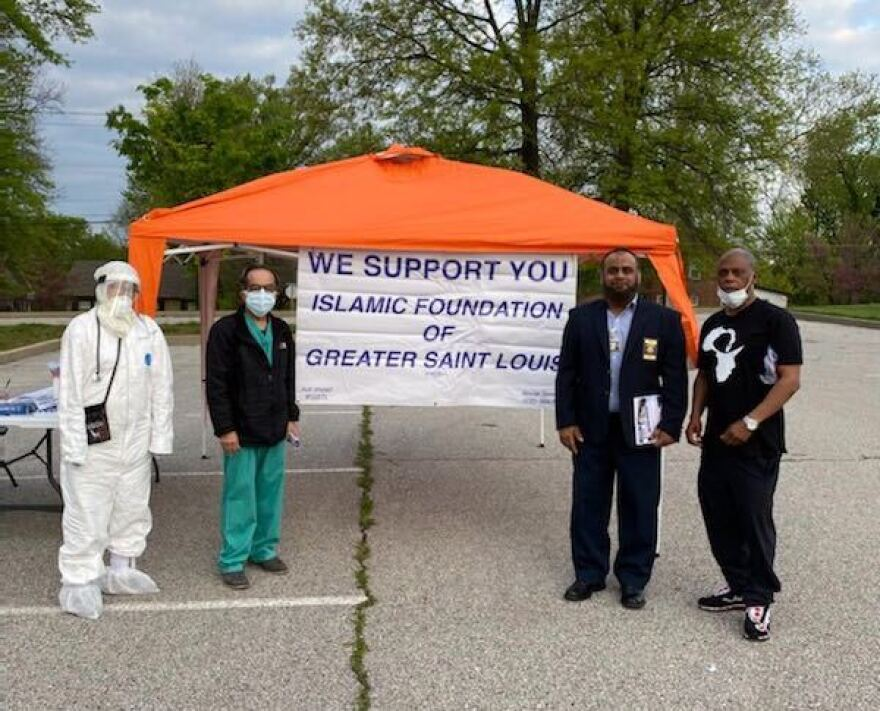 Dr. Mahrukh Khan (far left) and Malik Sims (far right) volunteering at the free, mobile COVID-19 testing spot in north Ferguson.