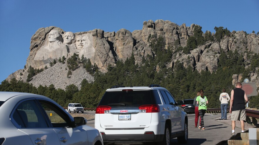 During the 2013 shutdown, tourists have to look at Mount Rushmore from the highway because the national memorial in Keystone, S.D., was closed.