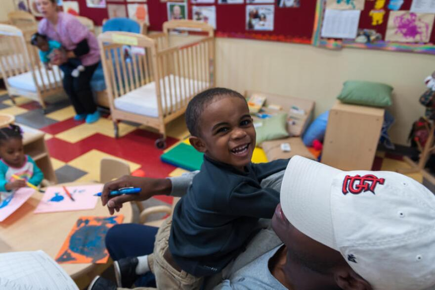 A father drops his son off at a YWCA Head Start day care in St. Louis in October 2017. Child care advocates worry there won't be enough care options this fall for parents to return to work.