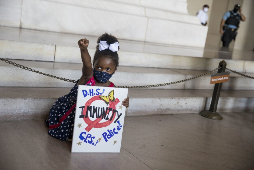 Laylah Pope, 5, poses at the foot of Lincoln's statue with her sign. She is from Detroit and was with her grandmother.