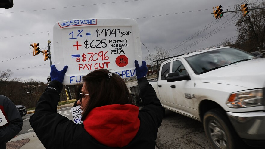 West Virginia teachers, students and supporters hold signs on a Morgantown, W.Va., street on Saturday. The strike is in its second weekend after the state Senate failed to pass the 5 percent raise teachers are demanding.