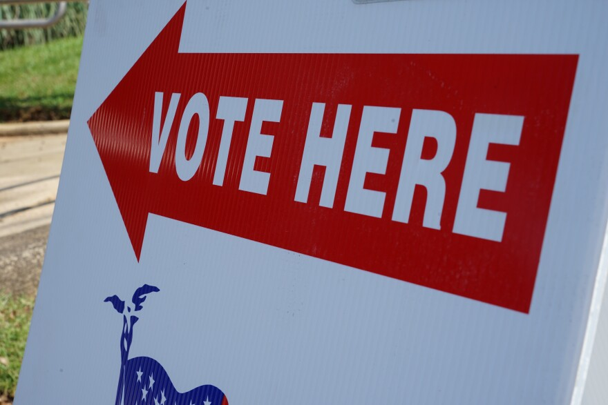 "Sign is placed on the sidewalk. It has a big arrow with the words, ""vote here,"" written on it."