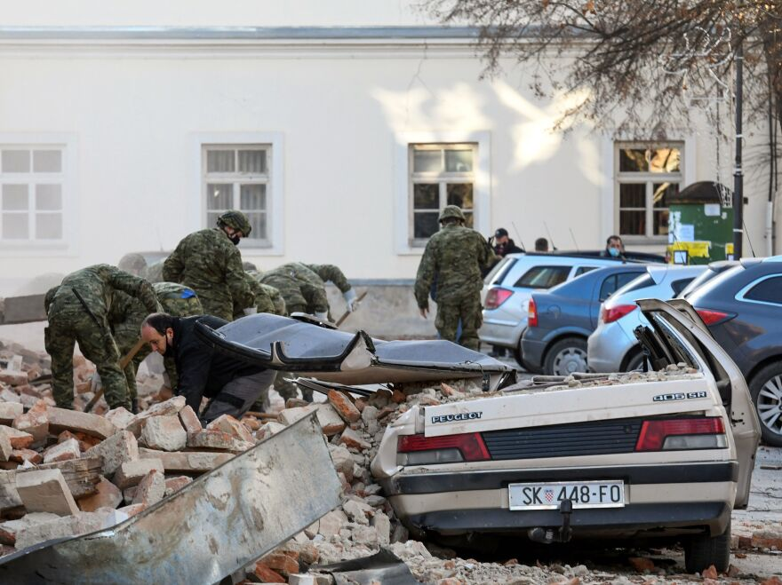 Croatian soldiers clean rubble next to damaged buildings in Petrinja, a town of about 24,000 residents.