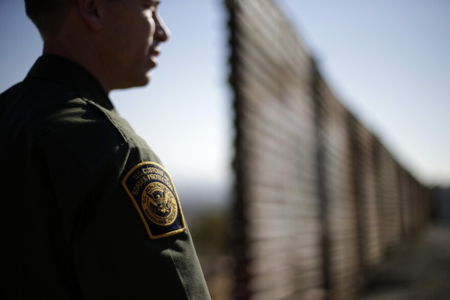 A Border Patrol agent looks to the north near where the border wall ends as it separates Tijuana, Mexico, (left) and San Diego.