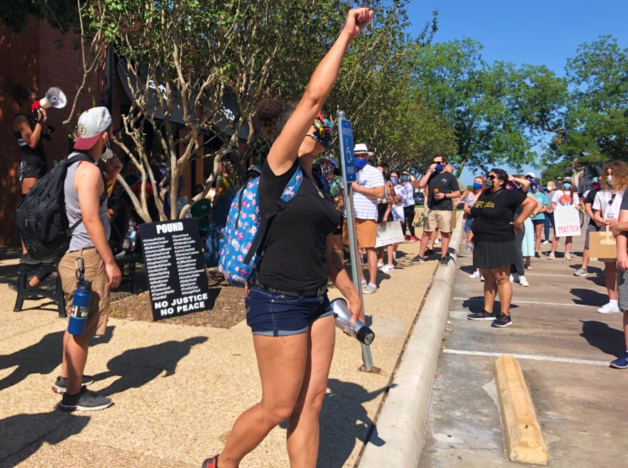 Ananda Tomas leads protestors in a practice chant before the march to Alamo Heights City Hall June 6, 2020.