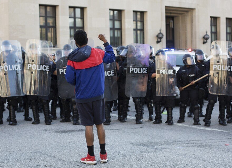 A protester stands in front of a line of St. Louis Police officers on Sept. 15, 2017.