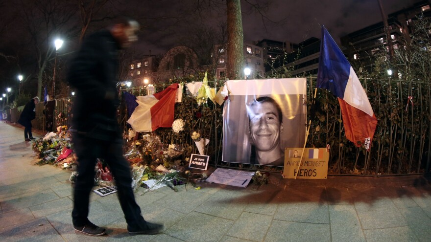 A man walks past a makeshift memorial for French Muslim policeman Ahmed Merabet near the site where he was shot dead by gunmen, close to the headquarters of the French satirical weekly <em>Charlie Hebdo.</em>