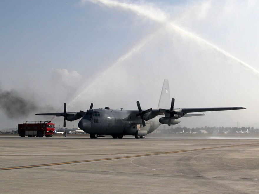 One of the Afghan air force's C-130 cargo planes passes under the spray of a pair of fire trucks at Kabul airport last month. The U.S. officially transferred the first two of four C-130s to the Afghans.