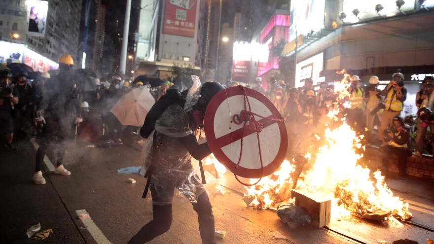 A protester uses a shield to cover himself as he faces police in Hong Kong on Saturday.