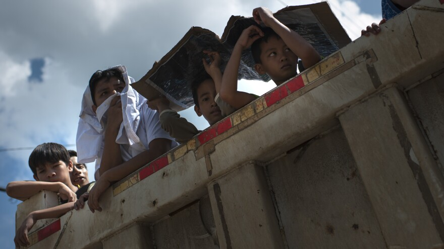 Children look on as they're transported from one section of Marawi to another, safer section on Saturday.