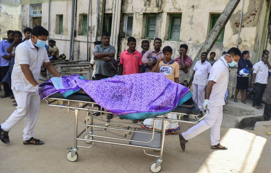Hospital workers transport a body on a stretcher at a hospital morgue following the explosion at a church in Batticaloa.