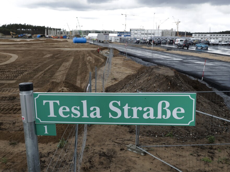 """A street sign says """"Tesla Street 1"""" in front of the construction site of the Tesla Gigafactory near Berlin. The electric automaker plans to start building cars this summer at its first European production site."""