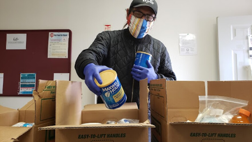 Photo of a man wearing a mask and pulling food out of boxes