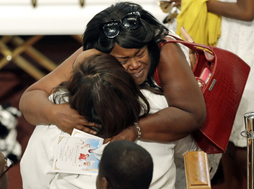 Tia Coleman is comforted by a guest during a funeral for her husband, Glenn Coleman, and her children, Reece Coleman, Evan Coleman and Arya Coleman, Friday, July 27, 2018, in Indianapolis. Nine members of the Coleman family were killed in a duck boat accident at Table Rock Lake near Branson, Mo.