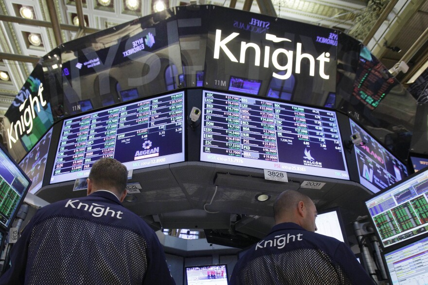 A pair of Knight Capital traders work at their post on the floor of the New York Stock Exchange before the close of trading Aug. 3, 2012. Knight Capital's stock soared after the battered trading firm received a financial lifeline and clients said they expect to resume routing trades through the system.
