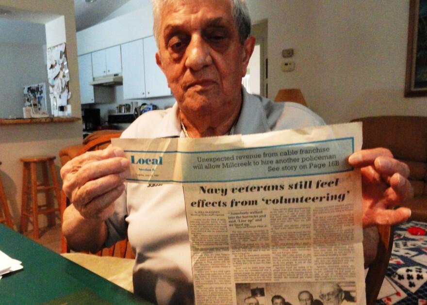 John_holding_newspaper_clipping.jpg