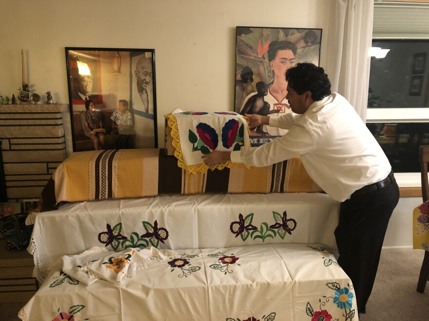 Man decorates ofrenda with floral sheets.