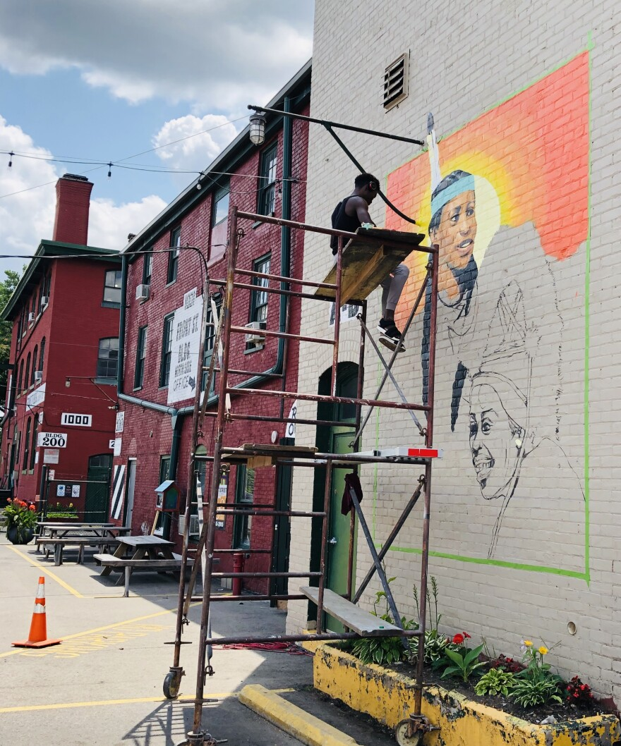 Patrick Gono working on the Front Street Mural.