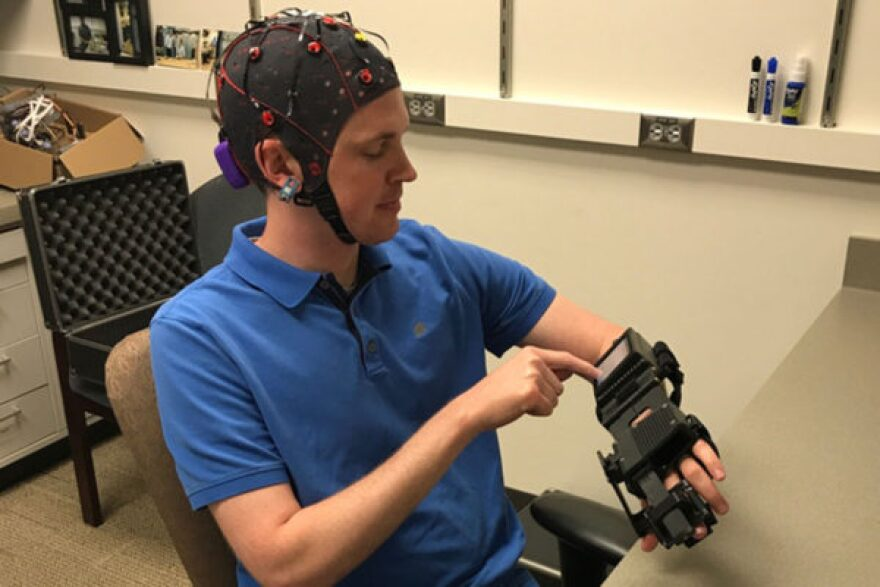 Washington University graduate student Jarod Roland tries out a device that detects electrical signals in his brain and casues his hand to open and close in response.