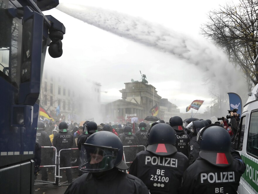 Police use water cannons to clear a road between the Brandenburg Gate and the Reichstag building, home of the German federal parliament, as people attend a protest rally in front of the Brandenburg Gate in Berlin on Wednesday.