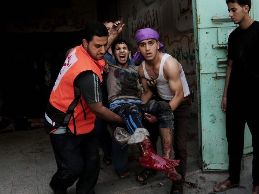 An injured man is carried to an ambulance following a strike in Gaza City's Shijaiyah neighborhood on Wednesday.
