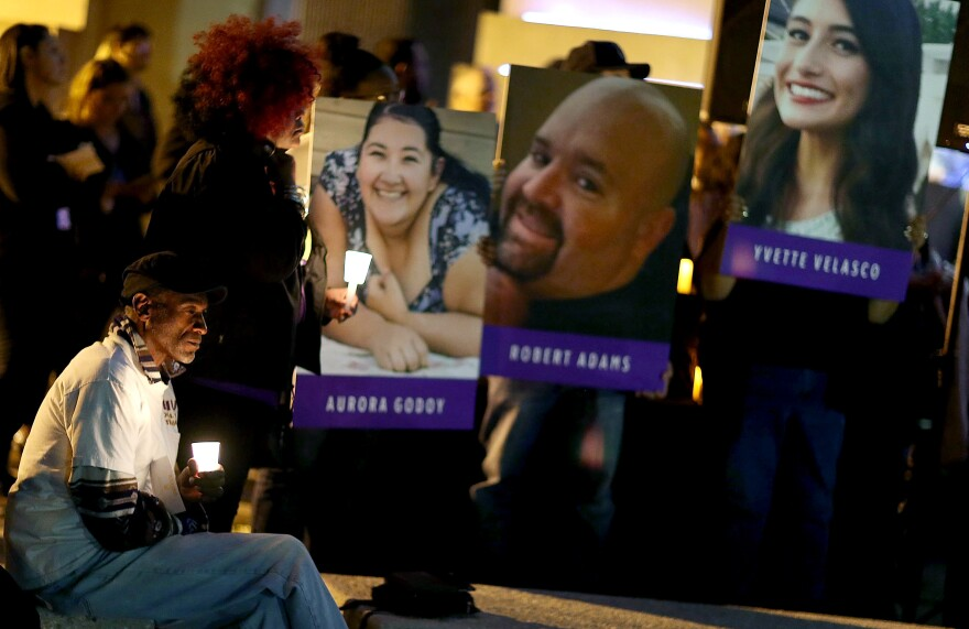 Photographs of victims of the terrorist attack on the Inland Regional Center are seen as people hold candles while attending a vigil at the San Bernardino County Board of Supervisors headquarters to remember those injured and killed during the shooting on Dec. 7, 2015, in San Bernardino, Calif.