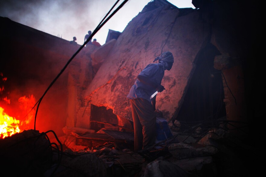 A man grips a knife as he looks for other looters to come out of a shop near downtown Port-au-Prince, Haiti.