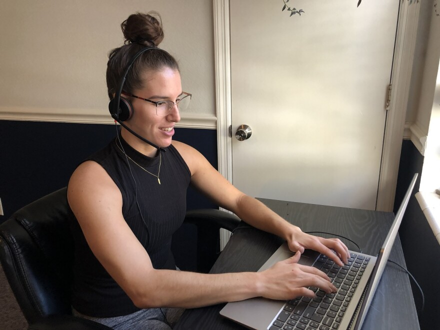 Helena Reid wears a headset and types on her laptop.