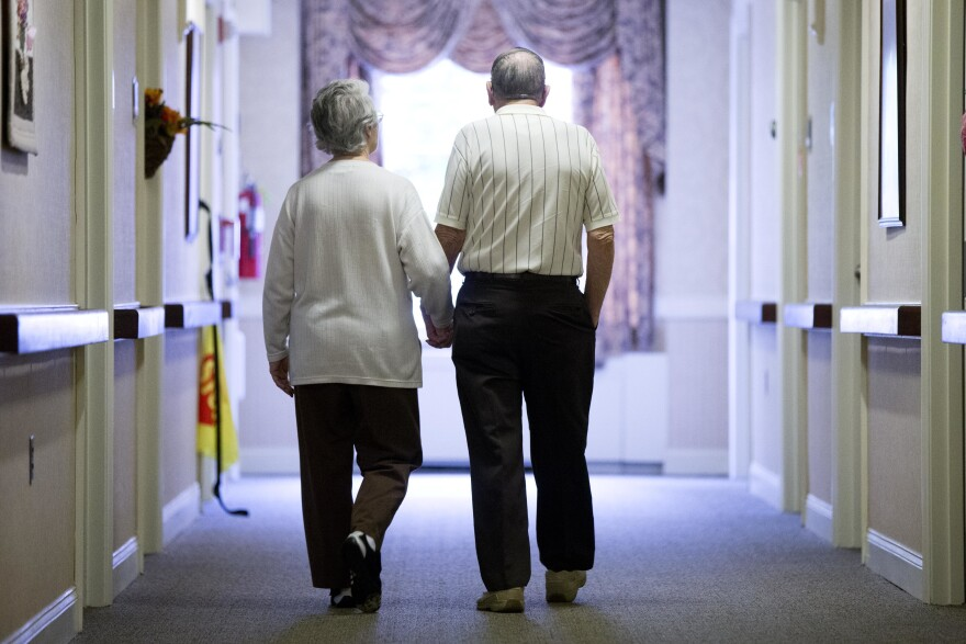 An elderly couple walks down a hall in Easton, Pa.
