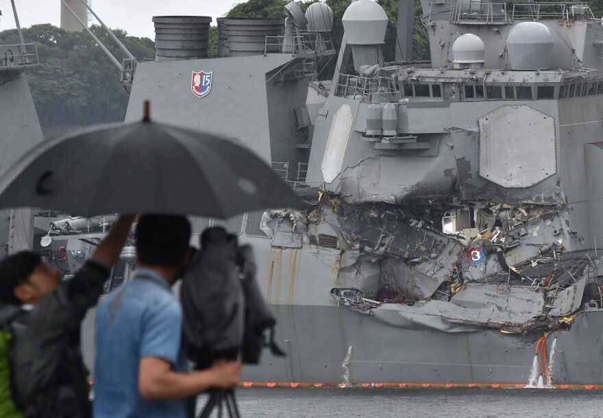 """A TV crew films the damage to the USS Fitzgerald at its port in Yokosuka, Japan, on Sunday. """"A number"""" of missing American sailors have been found dead in flooded areas of the destroyer, the U.S. Navy says."""