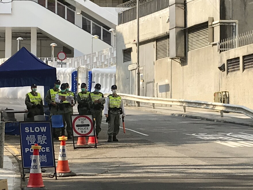 Hong Kong police guard a barricade outside the Chun Yeung public housing complex which has been turned in to the largest quarantine center in the city.