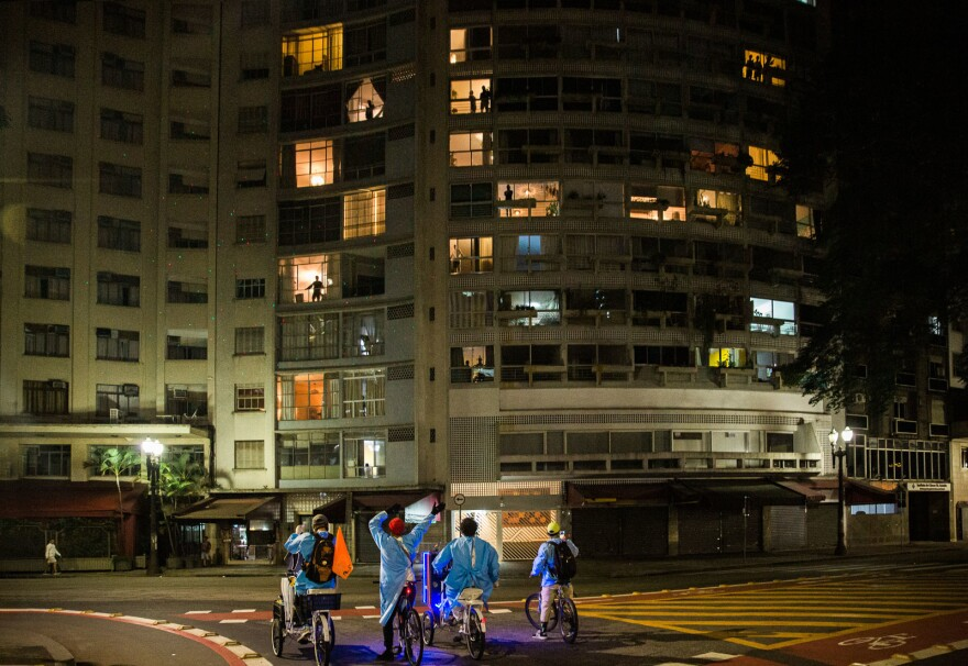 Four Brazilian men cycle around the center of São Paulo in protective gowns delivering protective masks and a mini cleaning kit to homeless people.