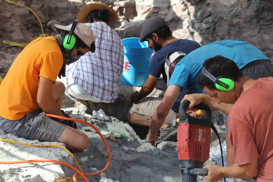 Photo of Three men wearing ear covers using power tools to drill into grey rock at the quarry.