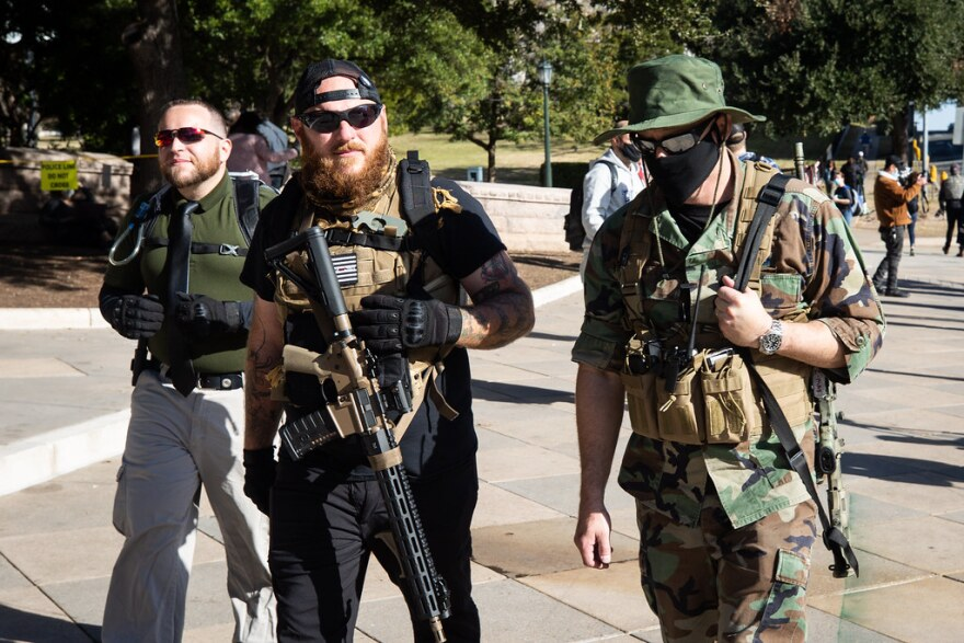Kris Hunter (center) and two other armed protesters join a small rally outside of the state Capitol grounds on Sunday.