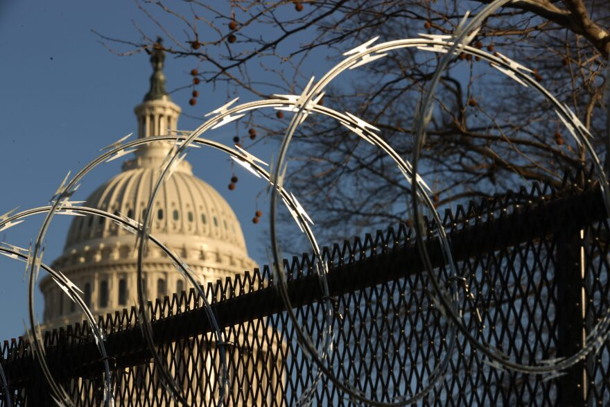 "Concertina razor wire tops the 8-foot ""non-scalable"" fence that surrounds the U.S. Capitol on the day after the House voted to impeach former President Trump for the second time. (Chip Somodevilla/Getty Images)"