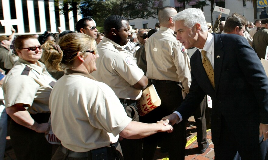 Woman in beige uniform shakes hands with a man who is in a black suit. People are behind them.