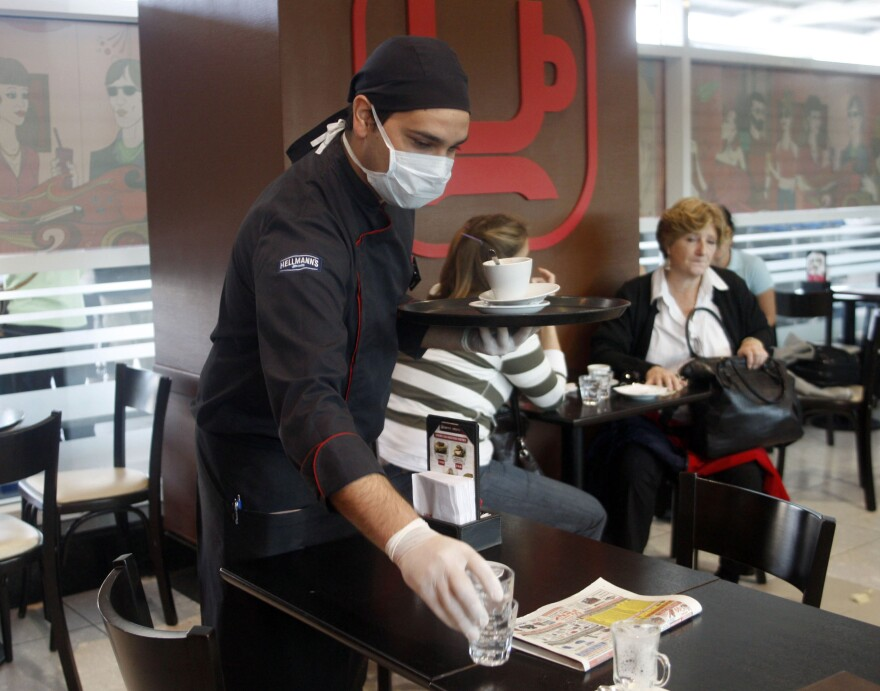 A waiter wearing a protective mask clears a table at a restaurant in Buenos Aires' airport April 28, 2009.