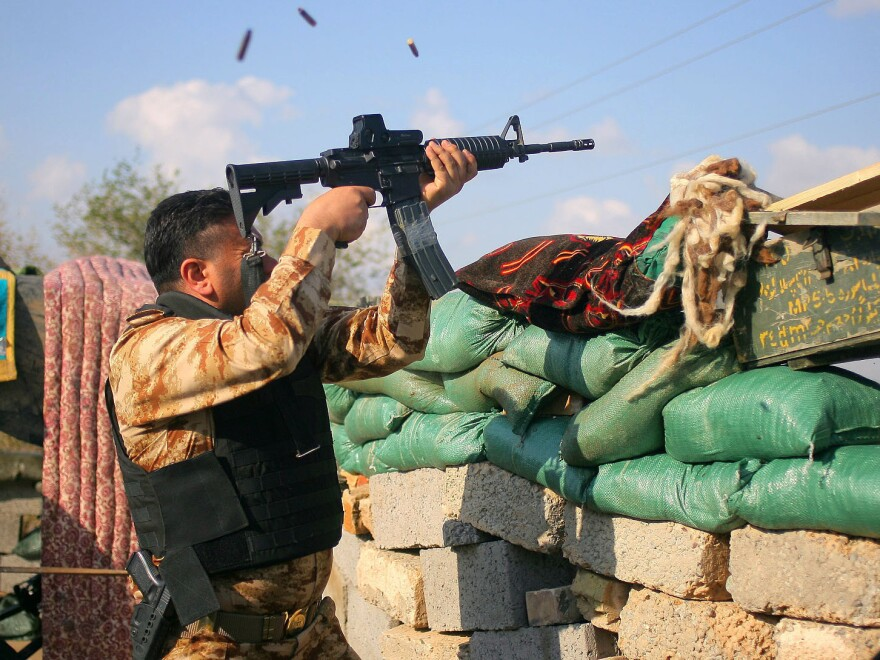 A volunteer fighter with a Shiite militant group known as Jihad Brigades fires his weapon during clashes with Islamic State  militants outside Tikrit, Iraq, on Saturday.