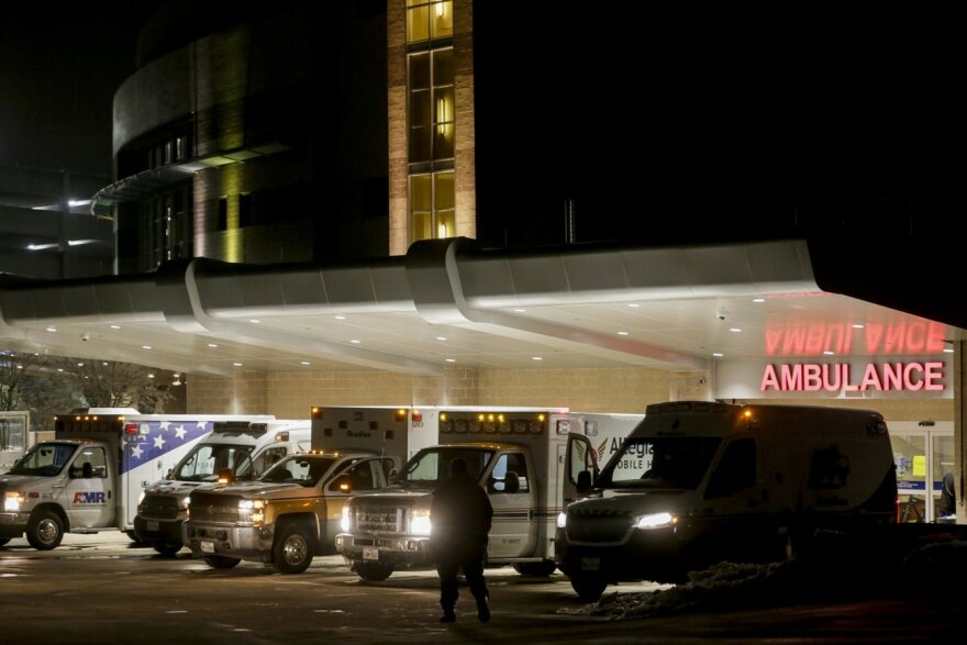 """Ambulances line up outside a hospital at night. They are lined up under a sign that reads """"Ambulance""""."""
