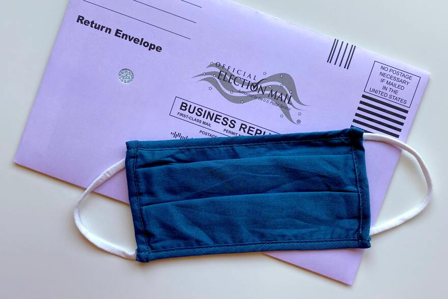 A blue medical mask in on top of a mail in ballot.