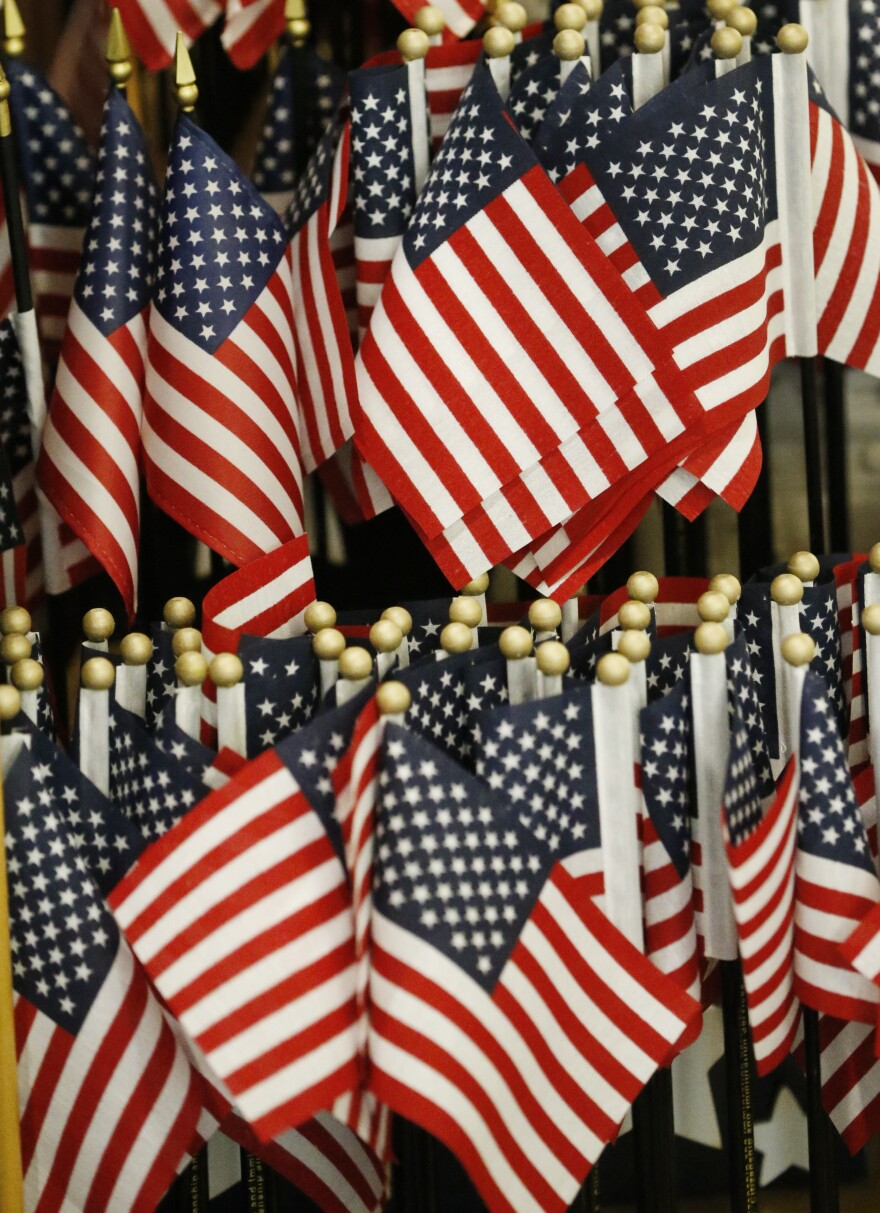 A display with American flags is shown during a naturalization ceremony at the U.S. Citizenship and Immigration Services Kendall Field Office, Thursday, Aug. 30, 2018, in Miami.