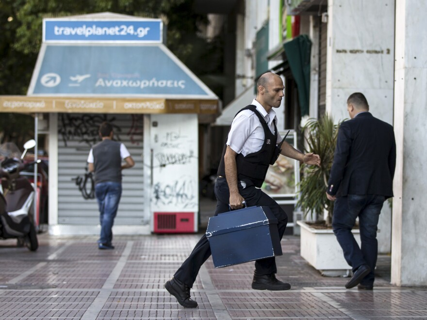 A security worker brings money to a National Bank branch in Athens on Sunday. Greeks have been withdrawing euros in anticipation of a possible default on the country's debt payments early next week.