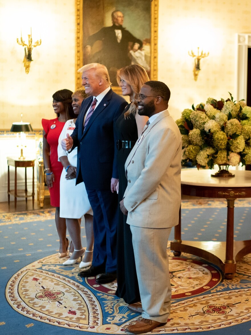 The family of United States Marine Capt. Jesse Melton III poses for a photo with President Donald Trump and First Lady Melania Trump during the reception.