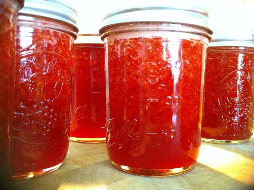 A few jars of strawberry jam bask in the light of what made them: the summer sun.