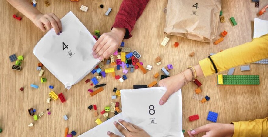 Legos on a table with numbered paper bags