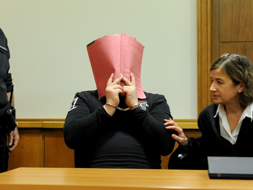 German police say they have evidence that former nurse Niels Högel murdered at least 84 people. He was already convicted in 2015 of two other murders. Above, Högel covers his face with a folder next to his lawyer in German regional court in 2014.