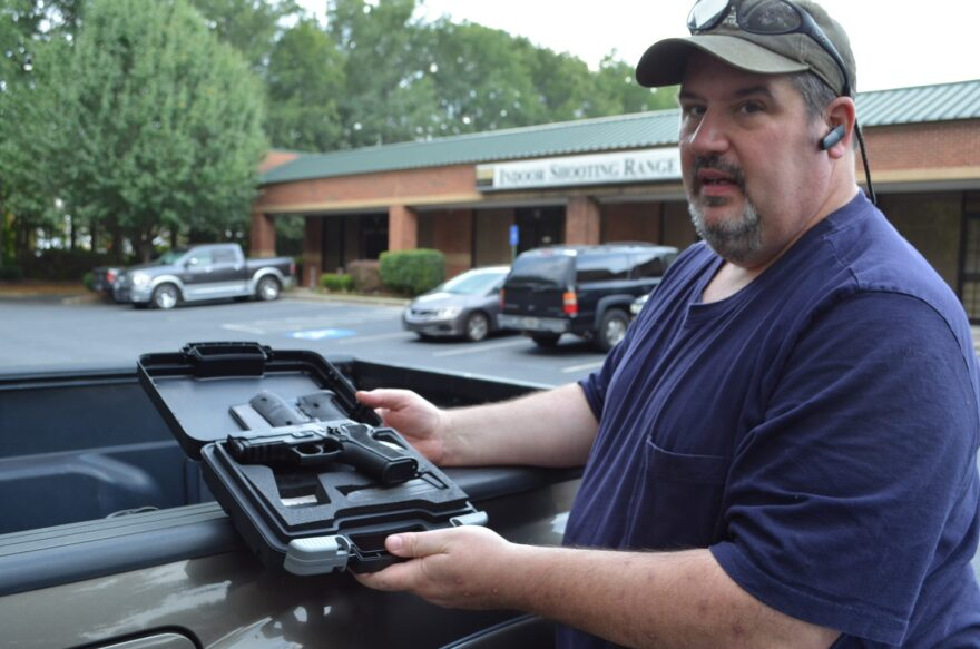 John Pander with the pistol he's been trying to sell online. Such private sales don't require a background check in Georgia.