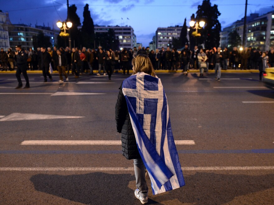 A woman wrapped in a Greek flag makes her way in to a demonstration to support the new anti-austerity government in Athens on Thursday.
